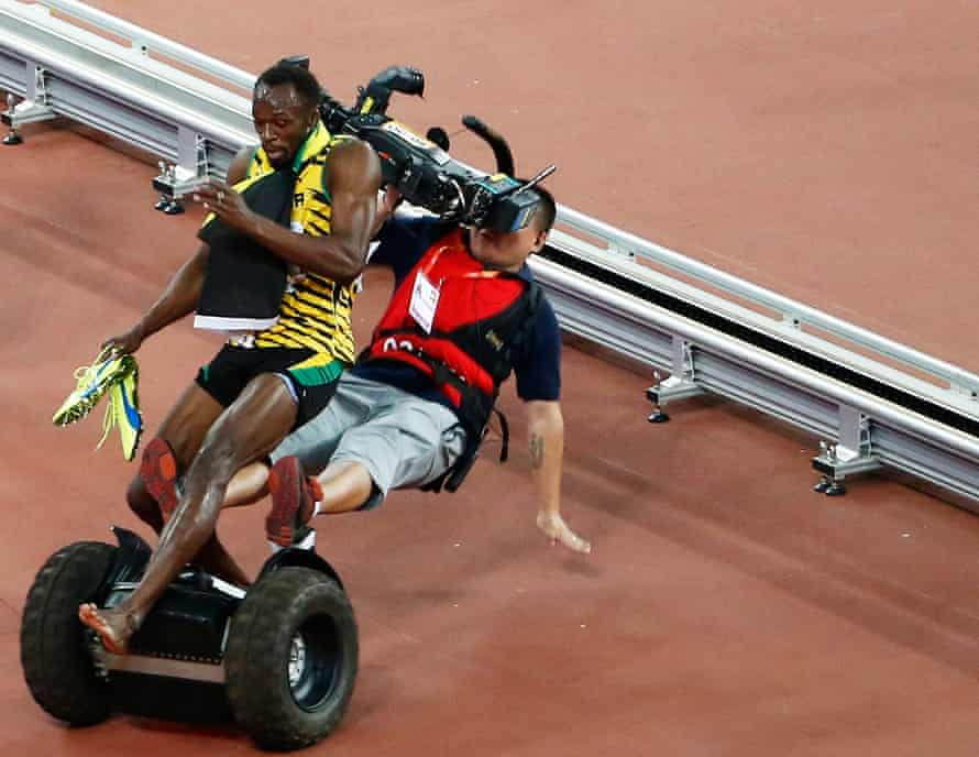 A Tv cameraman drives into Usain Bolt of Jamaica after the men's 200m final during the Beijing 2015 IAAF World Championships