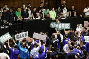 Lawmakers from Taiwan's ruling Democratic Progressive party (DPP) argue with politicians from the main opposition Kuomintang party (KMT) inside the parliament in Taipei