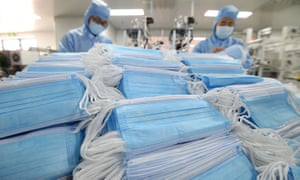 Employees work on a production line of disposable medical masks at a factory in Handan, Hebei province
