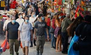 Shoppers wearing protective masks walk through the Shuk HaCarmel, or the Carmel market, in Tel Aviv.