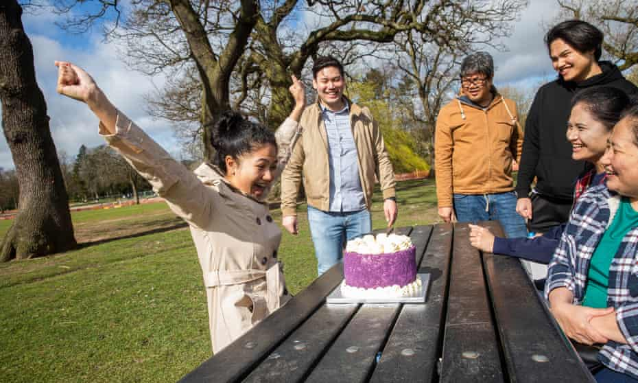 Allyssa Bravo, left, a nurse, with her fiance, Paul Abuston, second left, celebrate her 27th birthday in Cannon Hill park in Birmingham with family members.