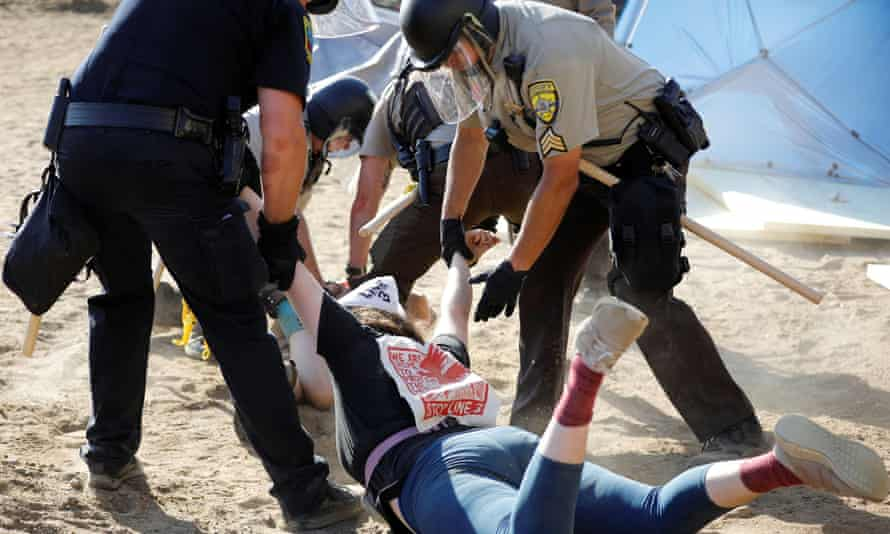 Police officers drag a demonstrator who was protesting at an Enbridge pump station construction site in Hubbard county, Minnesota, 7 June 2021.