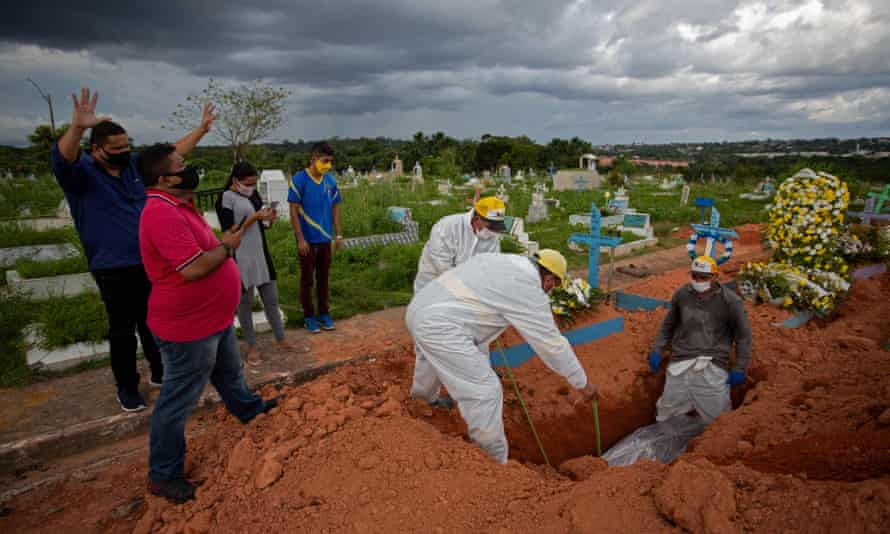Relatives pray during the funeral of a 57-year-old Covid victim at the Nossa Senhora Aparecida cemetery in Manaus, Brazil.