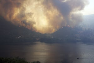 A forest fire rages on hills across the Tagus river on 27 July, near Vila Velha de Rodao, central Portugal.