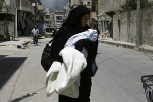 Manbij, Syria A woman carries her baby on a street as civilians fleeing the zones controlled by the Islamic State (IS) group arrive in the northern Syrian town, a day after Syrian Democratic Forces (SDF) retook it from IS.