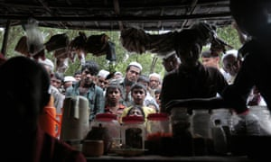 Rohingya at a refugee camp in Teknaf, near Cox's Bazar in Bangladesh, watch a news bulletin about government plans to relocate them to the island of Thengar Char