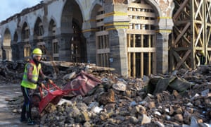 """An Iraqi worker clears rubble during the reconstruction of the Great Mosque of Al-Nuri, in Mosul's war-ravaged old town, on December 15, 2019. The famed complex including the 12th century mosque and its 8th century leaning minaret dubbed """"Al-Hadba"""" or """"the hunchback"""", was where the chief of the Islamic State group Abu Bakr al-Baghdadi declared a self-styled """"caliphate"""" after sweeping into Mosul in 2014. It was destroyed in fighting three years later."""