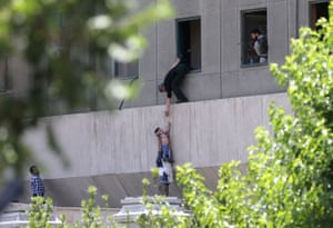 Tehran, Iran: Police officers evacuate a child from the parliament building during an attack