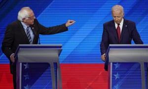 Senator Bernie Sanders, left, speaks to former vice-president Joe Biden.