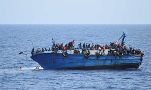 Migrants on a capsizing boat before a rescue operation by Italian navy ships off the coast of Libya.