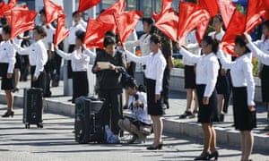 Women wave red flags next to the road in central Pyongyang. North Korea