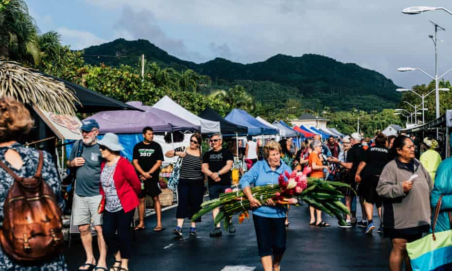 Tourists mix with locals at a market in Rarotonga, Cook Islands.
