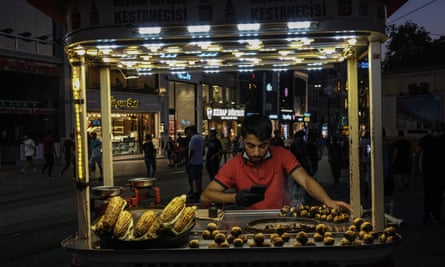A street seller checks the messages on his mobile phone in Taksim Square, Istanbul.