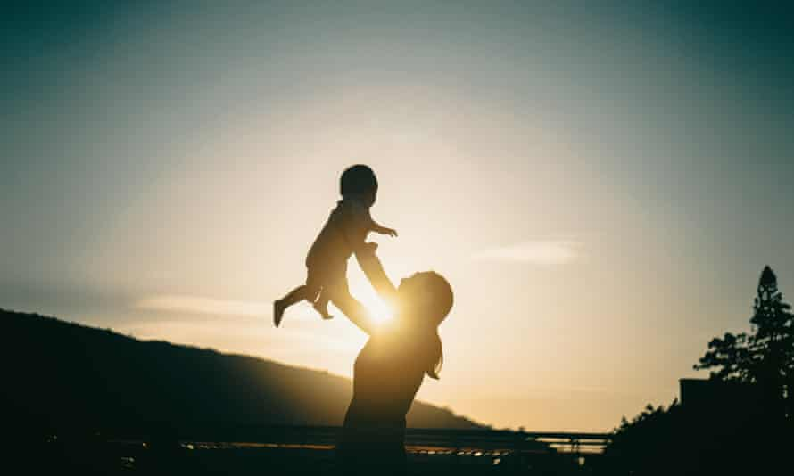 Silhouette of mother holding up baby in the air outdoors against sky during sunset