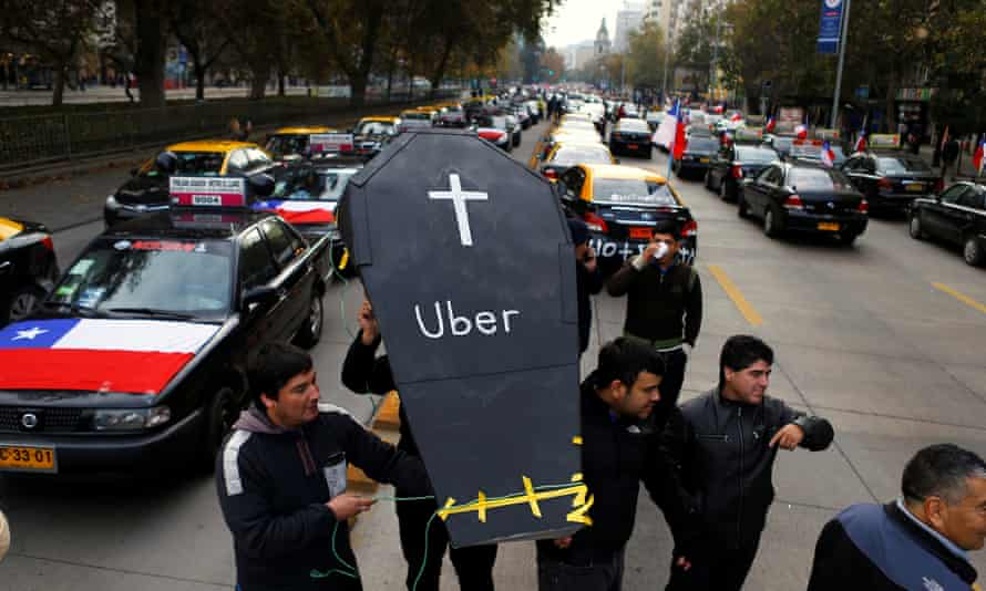 Taxi drivers carry a fake coffin as they block a street during a protest against Uber in Santiago, Chile, May 2016.