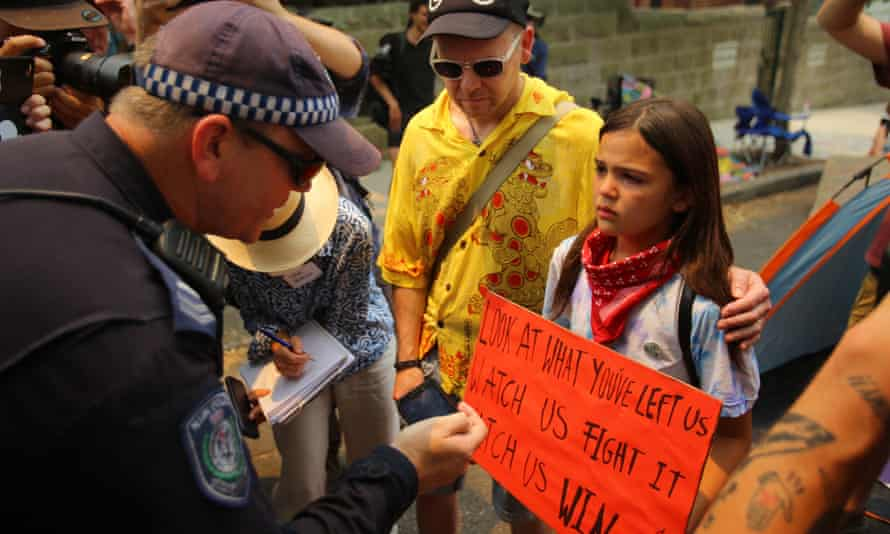 A policeman talks to Izzy Raj-Seppings during a protest outside Kirribilli House in Sydney