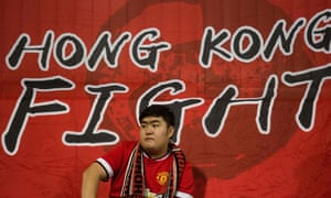A Hong Kong fan sits in front of a flag before the friendly between Hong Kong and Bahrain.
