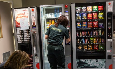 An ambulance worker gets some refreshments from a vending machin