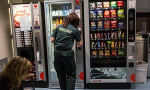 An ambulance worker buys snacks from a vending machine.