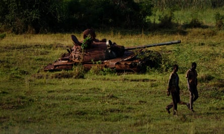 Two South Sudanese government soldiers walk past a disused tank in Bentiu, South Sudan
