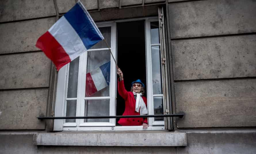 a Parisian woman waves a flag to pay tribute to essential workers during the Coronavirus outbreak in france