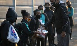 Schoolchildren in Johannesburg have their hands sanitised.