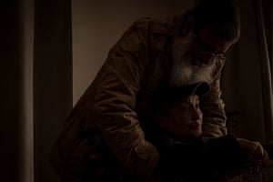 Jose comforts Gladys in the late afternoon light in the living room of Chelsea Wing.