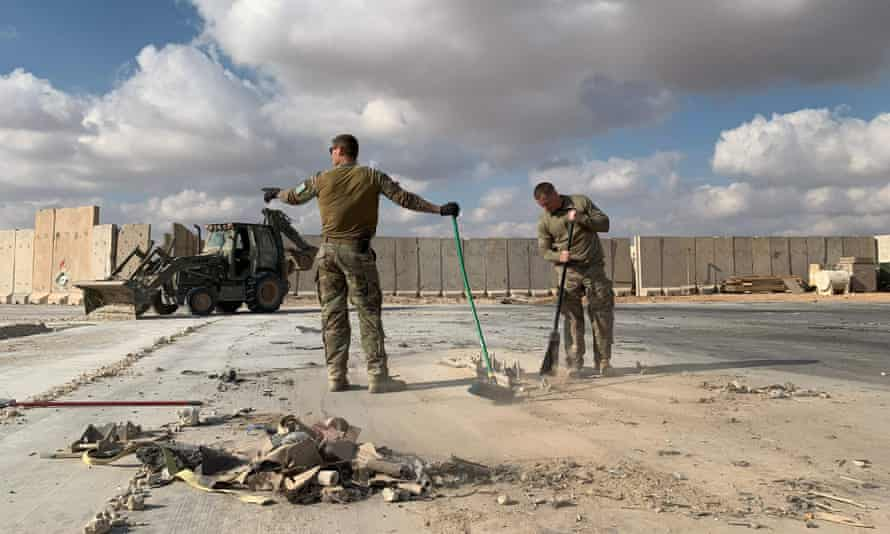 """US soldiers clear rubble at Ain al-Asad military airbase in the western Iraq province of Anbar on 13 January. (FILES) A file picture taken on January 13, 2020 during a press tour organized by the US-led coalition fighting the remnants of the Islamic State group, shows US soldiers clearing rubble at Ain al-Asad military airbase in the western Iraqi province of Anbar. - Nearly three dozen US troops suffered traumatic brain injuries or concussion in the recent Iranian air strike on a military base in Iraq housing American personnel, the Pentagon said on January 24, 2020. """"Thirty-four total members have been diagonosed with concussions and TBI (traumatic brain injury),"""" Pentagon spokesman Jonathan Hoffman told reporters. (Photo by Ayman HENNA / AFP) (Photo by AYMAN HENNA/AFP via Getty Images)"""
