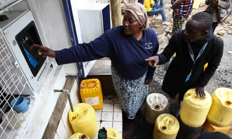 A woman is shown how to fetch water from one of the ATM-style water dispensers in the Mathare slums in Nairobi, Kenya.