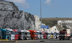 Cargo trucks wait to embark ferries in front of the white cliffs at the Port of Dover.