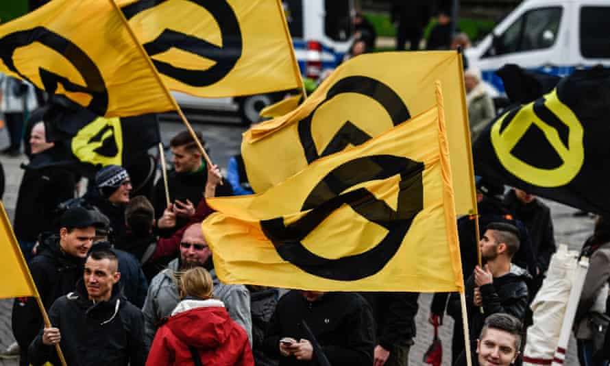 Protesters carry flags of the far-right Identitarian movement as they gather at a rally in Dresden, Germany, October 2017