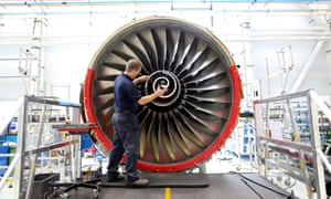 An employee fits the nose cone to a Trent 700 aircraft engine on the production line at the Rolls-Royce factory in Derby.