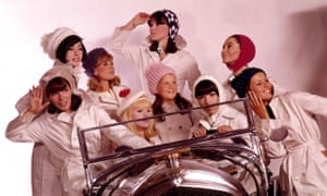 A group of young women wearing white coats, hats and bonnets as they crowd around a car in 1965