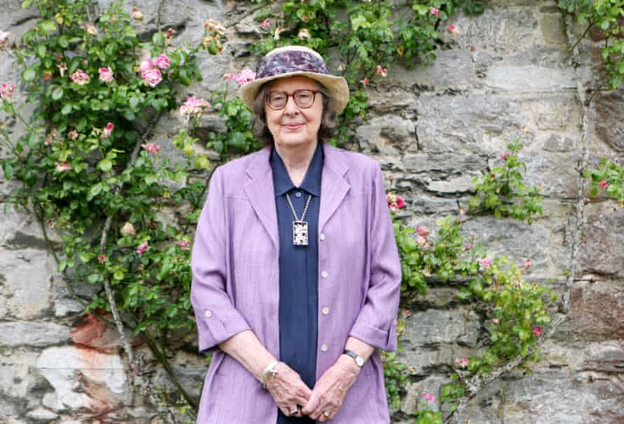 penelope lively standing by a garden well with climbing roses