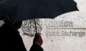 A man with an umbrella walks past the London Stock Exchange