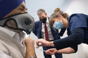 London, UK. The Labour leader, Sir Keir Starmer, watches as Dr Lizzie Goodman injects a patient with their first dose of the Pfizer/BioNTech Covid-19 vaccine at the Sir Ludwig Guttman Health and Wellbeing Centre in Stratford
