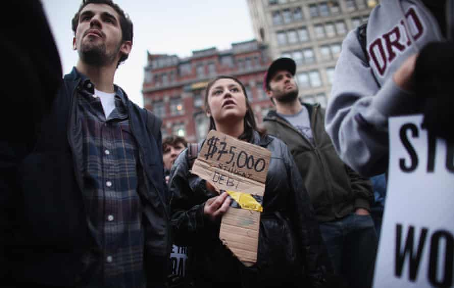 An Occupy protester holds a sign reading '$75,000 in student debt.'