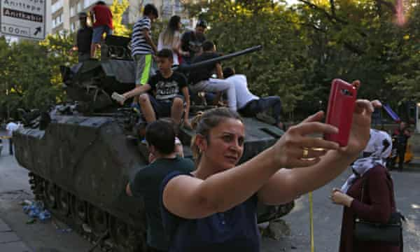 A woman takes a selfie in front of a damaged Turkish military vehicle.