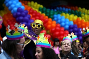 People wearing rainbow crowds in front of rainbow balloons