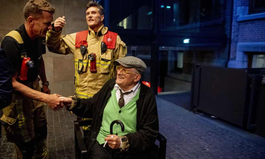 David Hockney, cigarette in hand, poses with his rescuers after he was stuck in an elevator in the Conservatorium Hotel in Amsterdam for almost half an hour.