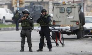 Israeli border police guard the scene where a Palestinian woman was shot dead by Israeli troops.