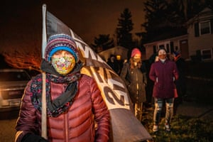 A woman holds a Black Lives Matter flag as she participates in a call to action White People Stop Calling the Cops on Black People protest hosted by Showing Up for Racial Justice Columbus(SURJ) in front of the house of the neighbour who called the police on Andre Hill the night he was shot and killed in Columbus, Ohio
