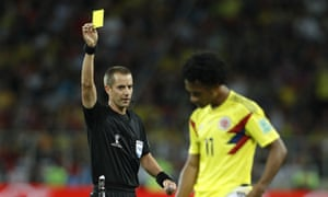 Referee Mark Geiger shows a yellow card to Colombia's Juan Cuadrado