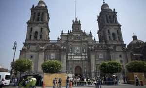 Reporters stand near the site where archaeologists found a stone slab near the cathedral in Mexico City.