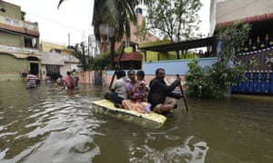 People use a makeshift boat to transfer to navigate the flooded streets of Chennai - water is waist high