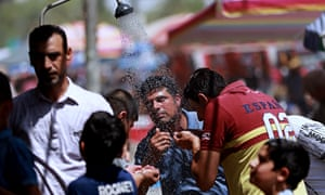 People cool off under an open-air shower in Baghdad as temperatures soar