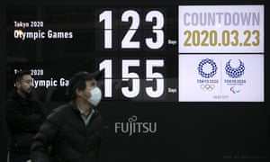 A man walks near a countdown display for the Tokyo 2020 Olympics and Paralympics in Tokyo, Monday, March 23, 2020.