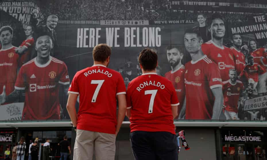 Two Manchester United fans wearing freshly bought Cristiano Ronaldo shirts look at the huge banner on the front of the stadium the day before his return match against Newcastle