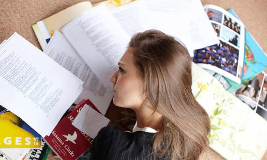 Young woman sitting on floor surrounded by papers and books, looking stressed