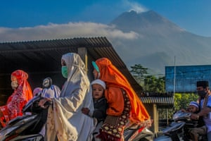Sleman, Indonesia: People travel home after prayers past Mount Merapi as it emits smoke